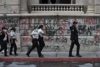 Police officers patrol in front of the Congress building that was damaged during protests in Guatemala City, Sunday, Nov. 22, 2020. Protesters broke into the building and set it partially on fire amid growing demonstrations against President Alejandro Giammattei and the legislature for approving a controversial budget that cut educational and health spending. (AP Photo/Moises Castillo)