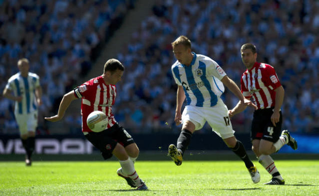 Huddersfield's Jordan Rhodes (2nd R) plays a pass past Sheffield United's Michael Doyle (2nd L) during the League 1 Play-Off Final football match between Huddersfield Town and Sheffield United at Wembley Stadium in London on May 26, 2012. AFP PHOTO / ADRIAN DENNISADRIAN DENNIS/AFP/GettyImages