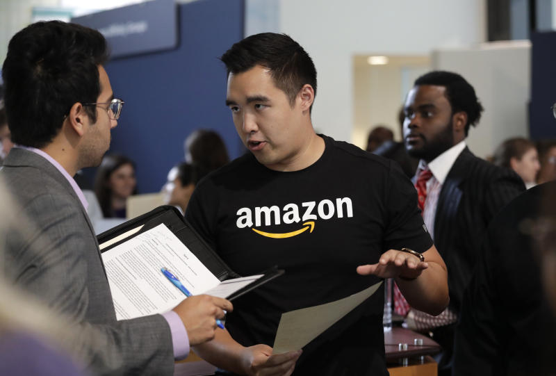 FILE - In this Sept. 17, 2019, file photo Amazon recruiter Perry Chang speaks with a prospective employee at a job fair hosted by the company. Amazon says it hired 200,000 people for the busy holiday shopping season, double the amount of people it hired last year. (AP Photo/Elaine Thompson, File)
