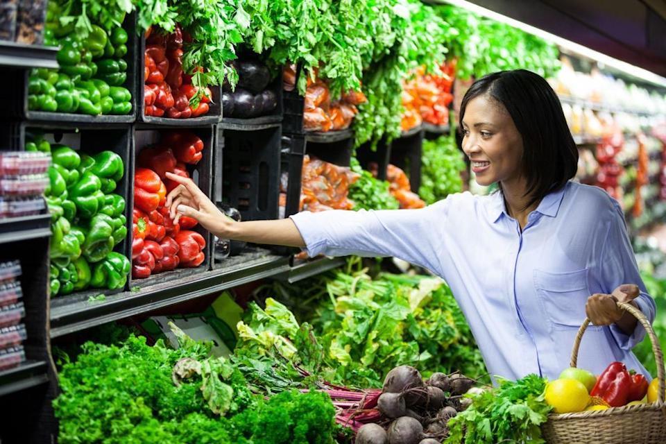 Woman buying vegetables in organic section of supermarket