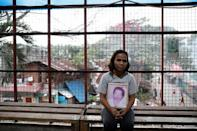 Kathrina Polo holds a picture of her late husband inside a church in Barangay Payatas district in Quezon City, Metro Manila in the Philippines December 11, 2017. REUTERS/Erik De Castro