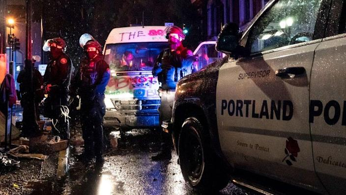 Police detain passengers in a mutual aid van during an Indigenous Peoples Day of Rage protest on October 11, 2020 in Portland, Oregon