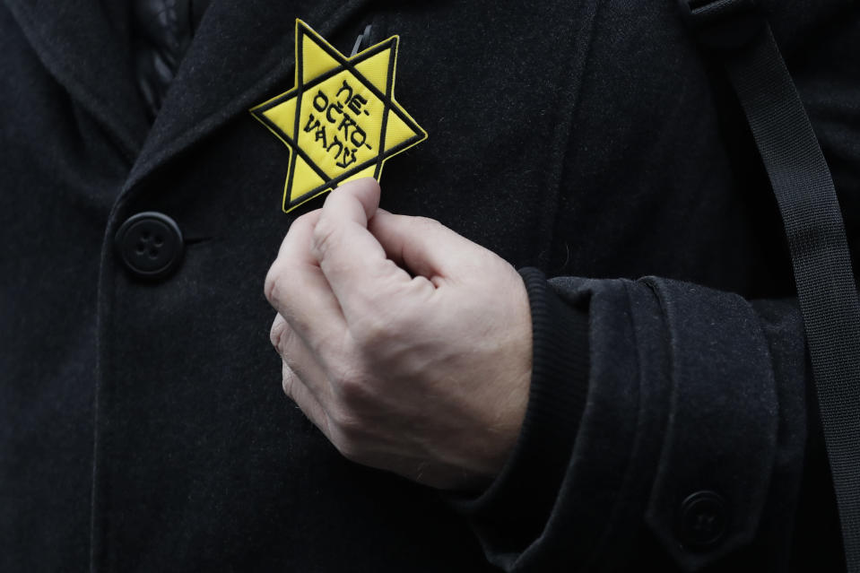 """In this photo taken Friday, Jan. 8, 2021, a protesters holds a cloth badge in the shape of the Jewish Star of David reading: """"unvaccinated"""" during a protest against the government's restrictive measures imposed to contain the coronavirus pandemic in Prague, Czech Republic. Across the Balkans and the rest of the nations in the southeastern corner of Europe, a vaccination campaign against the coronavirus is overshadowed by heated political debates or conspiracy theories that threaten to thwart the process. In countries like the Czech Republic, Serbia, Bosnia, Romania and Bulgaria, skeptics have ranged from former presidents to top athletes and doctors. Nations that once routinely went through mass inoculations under Communist leaders are deeply split over whether to take the vaccines at all. (AP Photo/Petr David Josek)"""