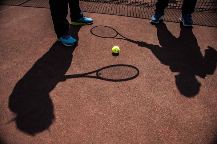 In this image take on Friday, April 24, 2020 the shadows of Italian Tennis Federation coaches Luca Brasi, 55, and his brother Daniele Brasi, 41, are cast on their tennis court in Rovetta, near Bergamo, northern Italy. The brothers, who lost an uncle to COVID-19, run one of the biggest Italian Tennis Federation centers in the valley. They rely on tourism for about 50% of their yearly income, the rest comes from roughly 900 school students who follow courses throughout the winter, including some 20 under-18 professionals. (AP Photo/Luca Bruno)
