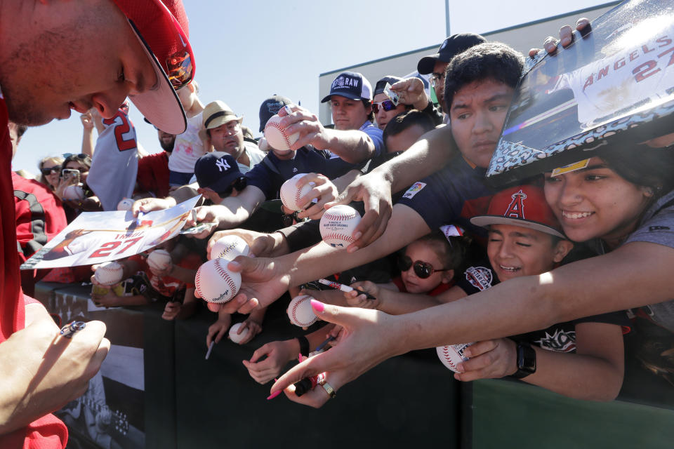 Fans squeeze forward as they try to get an autograph from Los Angeles Angels' Mike Trout before a spring training baseball game against the Seattle Mariners, Sunday, March 10, 2019, in Tempe, Ariz. (AP Photo/Elaine Thompson)