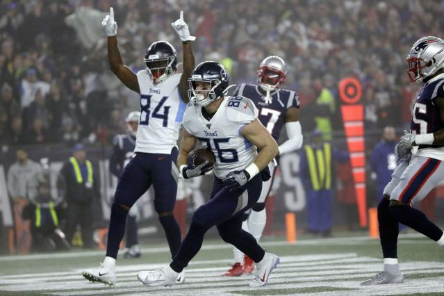 Tennessee Titans tight end Anthony Firkser, center, catches a touchdown pass against the New England Patriots as the Titans beat the Patriots in the wild-card round. (AP Photo/Elise Amendola)