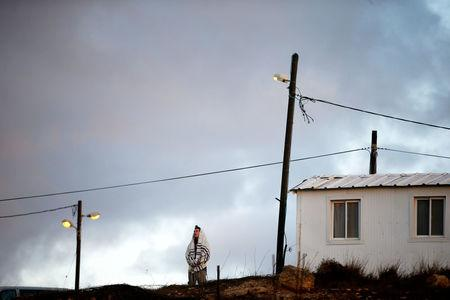 FILE PHOTO: An Israeli man wearing a Jewish prayer shawl, prays near a home in the early morning, in the Jewish settler outpost of Amona in the West Bank December 15, 2016. REUTERS/Ronen Zvulun/File Photo
