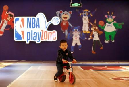 A boy plays outside the NBA Playzone at a shopping mall in Beijing