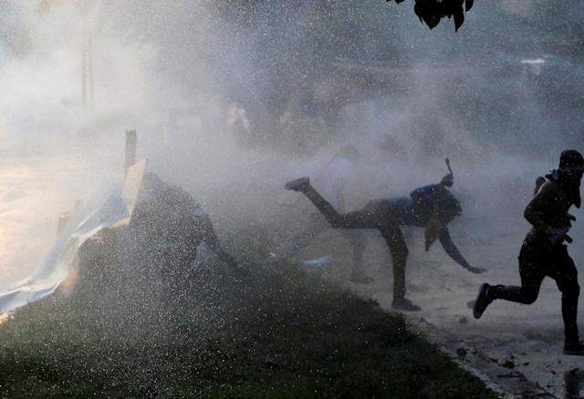 <p>Opposition party supporters are hit by a water cannon while clashing with riot security forces during a rally against President Nicolas Maduro in Caracas, Venezuela, May 18, 2017. (Marco Bello/Reuters) </p>