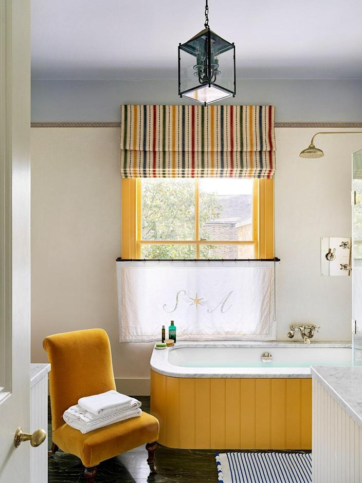 The pops of yellow in the primary bathroom thanks to Farrow & Ball's India Yellow uplift the period details.