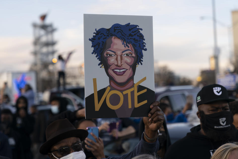 People in the crowd hold up an image of Stacey Abrams as President-elect Joe Biden speaks in Atlanta, Monday, Jan. 4, 2021, to campaign for Georgia Democratic candidates for U.S. Senate, Rev. Raphael Warnock and Jon Ossoff. (AP Photo/Carolyn Kaster)
