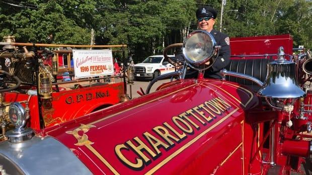 A uniformed individual sits atop a vintage fire engine during a past Gold Cup Parade. This year's event will look a little different, with floats visiting various neighbourhoods throughout Charlottetown. (Brian Higgins/CBC - image credit)