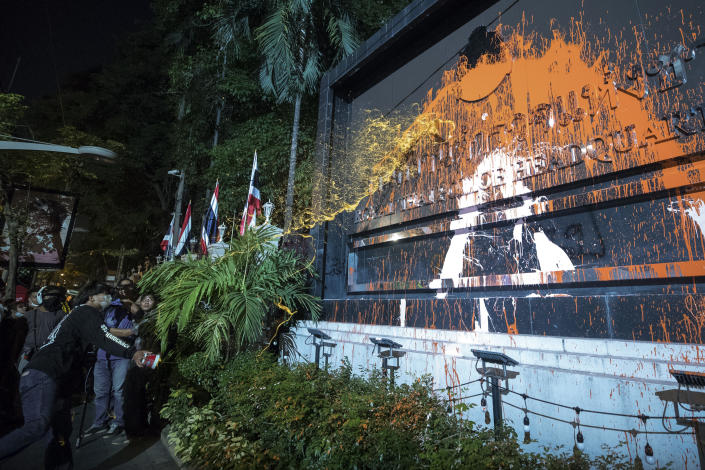 Pro-democracy protesters splash colored paint on the police headquarters sign in Bangkok, Thailand, Wednesday, Nov. 18, 2020. Police in Thailand's capital braced for possible trouble Wednesday, a day after a protest outside Parliament by pro-democracy demonstrators was marred by violence that left dozens of people injured. (AP Photo/Wason Wanichakorn)