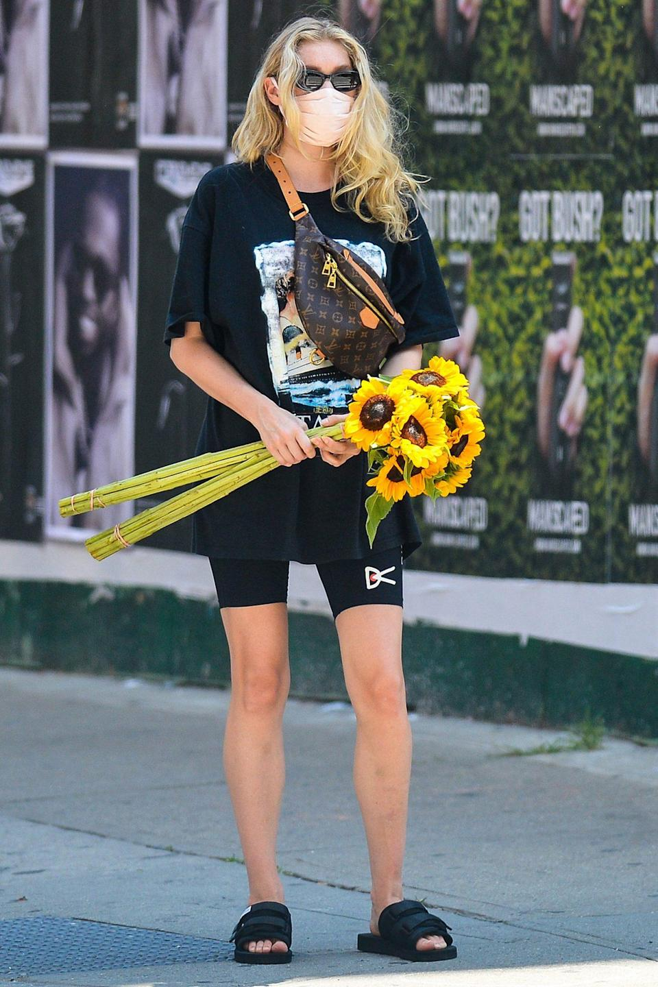 <p>Elsa Hosk makes her way through downtown N.Y.C. on Monday with a handful of sunflowers.</p>