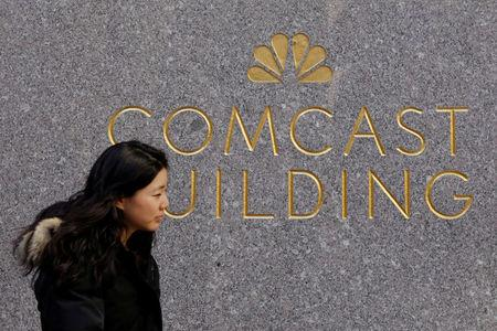 FILE PHOTO: A woman walks past the NBC and Comcast logos on 30 Rockefeller Plaza in midtown Manhattan in New York
