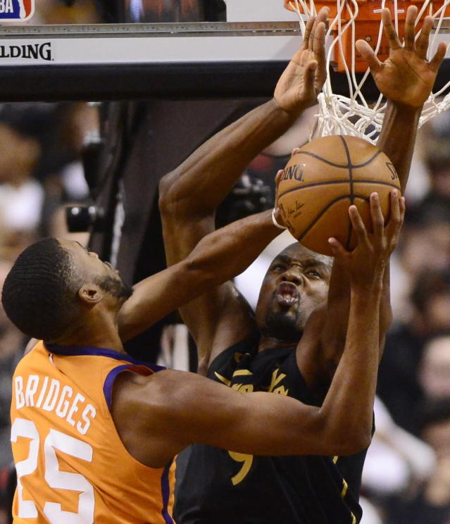 Toronto Raptors center Serge Ibaka (9) defends against Phoenix Suns forward Mikal Bridges (25) during the second half of an NBA basketball game Friday, Feb. 21, 2020, in Toronto. (Frank Gunn/The Canadian Press via AP)