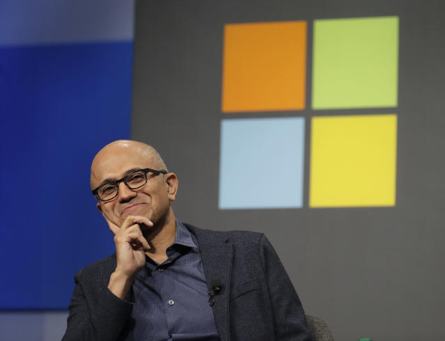 FILE- In this Wednesday, Nov. 28, 2018, file photo, Microsoft CEO Satya Nadella listens to a question as he sits in front of the Windows logo during the annual Microsoft Corp. shareholders meeting in Bellevue, Wash. The MLS soccer Seattle Sounders team announced Tuesday, Aug. 13, 2019 that they are adding Nadella and his wife Anu to club's ownership group, along with Seattle Seahawks quarterback Russell Wilson, hip-hop artist Macklemore, and several others as Hollywood producer Joe Roth leaves the franchise. (AP Photo/Ted S. Warren, File)