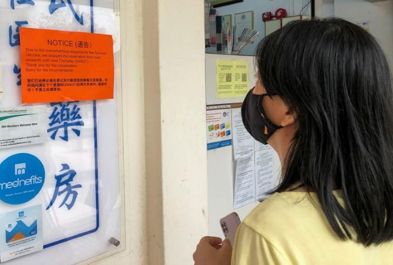 """A woman reads a notice sign about """"overwhelming response"""" for the Sinovac vaccine at a clinic, during the coronavirus disease (COVID-19) outbreak in Singapore"""