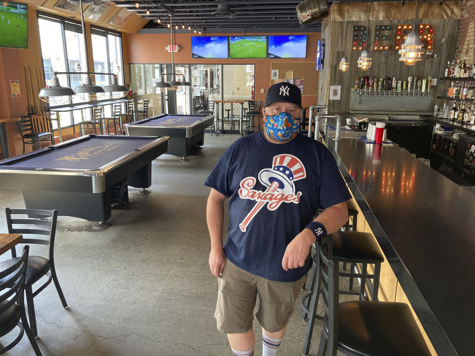 Flattop Pizza bartender Mike Miller poses for a photo at the restaurant in downtown Anchorage, Alaska, Wednesday, July 1 2020, the same day Alaska residents began receiving their share of the state's oil wealth. Miller says the $992 check that hit his account early Wednesday morning was a nice little boost as his extended unemployment runs out. (AP Photo/Mark Thiessen)