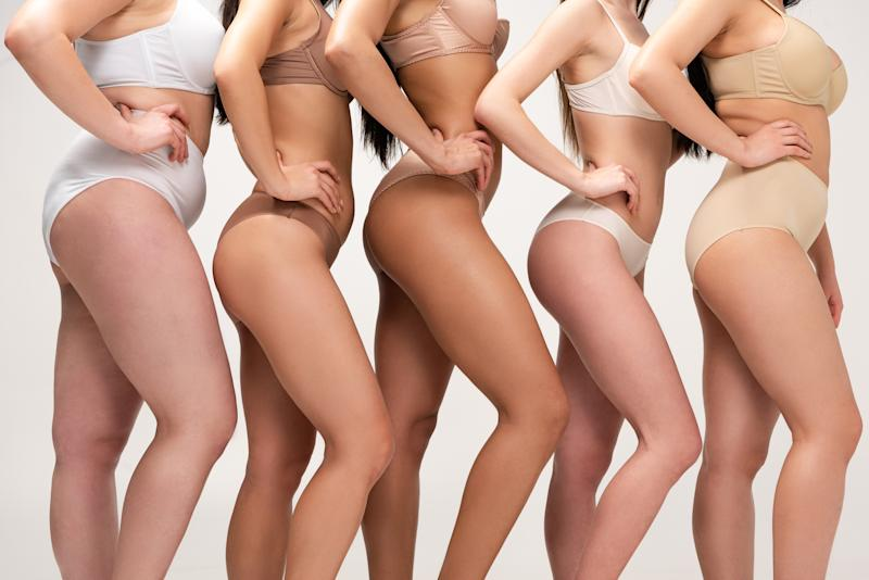 cropped view of five multiethnic women in underwear posing with hands on hips isolated on grey, body positivity concept