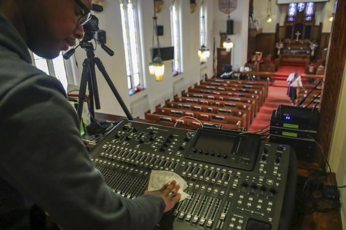 Multimedia technician Joseph Stoute, 21, use a disinfectant wipe to clean the audio equipment at St. Paul's Methodist Church in Brooklyn, New York, where he directed a livestream online broadcast Sunday for homebound congregants due to citywide restrictions aimed at controlling the COVID-19 outbreak. (AP Photo/Bebeto Matthews)