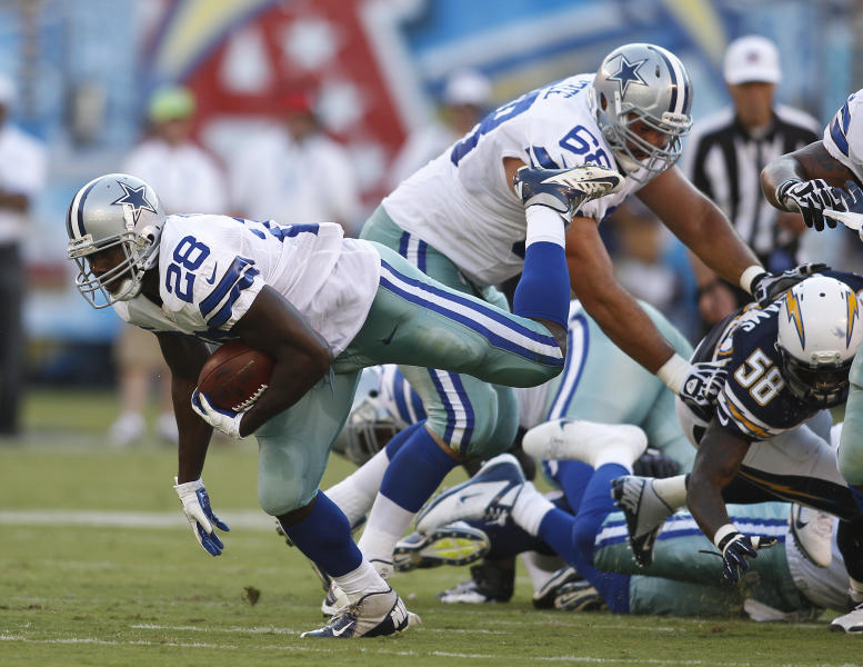 Dallas Cowboys running back Felix Jones tries to keep his balance as he slides through the San Diego Chargers defense during the first half of a NFL preseason football game Saturday, Aug. 18, 2012 in San Diego. (AP Photo/Chris Park)