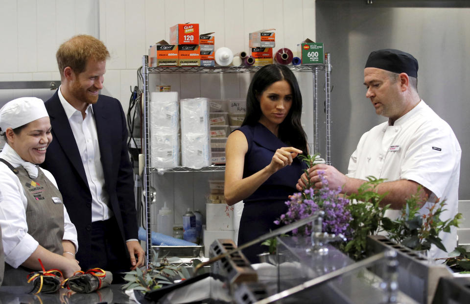 Britain's Prince Harry and his wife, Meghan, Duchess of Sussex, look at traditional native Australian ingredients during a visit to Mission Australia social enterprise restaurant, Charcoal Lane, in Melbourne, Australia, Thursday, Oct. 18, 2018. Prince Harry and his wife Meghan are on day three of their 16-day tour of Australia and the South Pacific. (Phil Noble/Pool Photo via AP)