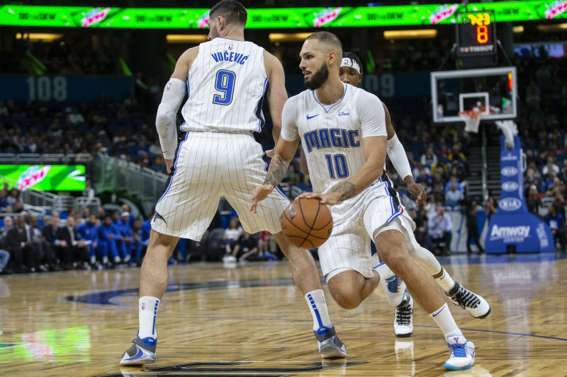 Orlando Magic guard Evan Fournier (10) dribbles by center Nikola Vucevic (9) and Philadelphia 76ers guard Josh Richardson during the first half of an NBA basketball game in Orlando, Fla., Friday, Dec. 27, 2019. (AP Photo/Willie J. Allen Jr.)