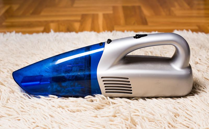 Handheld vacuum cleaner standing on white fluffy carpet with parquet in background. Housekeeping concept