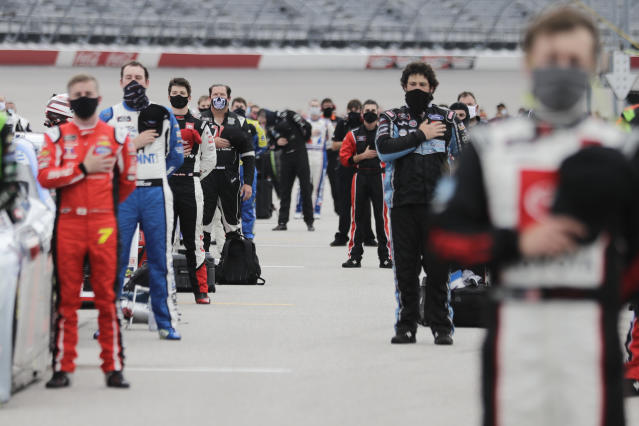 Drivers stand for the national anthem before the Toyota 200 NASCAR Xfinity series auto race Thursday, May 21, 2020, in Darlington, S.C. (AP Photo/Brynn Anderson)