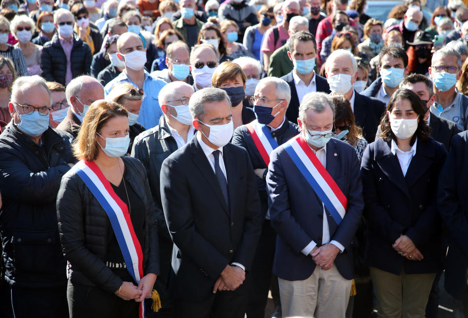The sub prefect Herve Jonathan, second left, surrounded by local elected officials, observe a minute of silence in Bayonne, southwestern France, Sunday, Oct. 18, 2020, in memory of the teacher Samuel Paty. Demonstrations around France have been called in support of freedom of speech and to pay tribute to a French history teacher who was beheaded near Paris after discussing caricatures of Islam's Prophet Muhammad with his class. (AP Photo/Bob Edme)