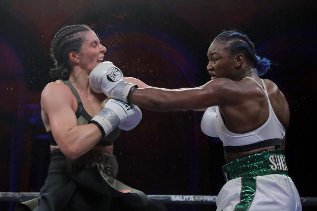 Claressa Shields, right, lands a left to Christina Hammer during the 10th round of a women's middleweight championship boxing bout Saturday, April 13, 2019, in Atlantic City, N.J. Shields won by unanimous decision. (AP Photo/Julio Cortez)