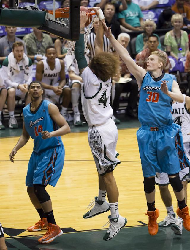 Hawaii forward Isaac Fotu, center, dunks as Oregon State forwards Devon Collier (44) and Olaf Schaftenaar (30) defend during the second half of an NCAA college basketball game at the Diamond Head Classic on Wednesday, Dec. 25, 2013, in Honolulu. Hawaii won 79-73. (AP Photo/Eugene Tanner)