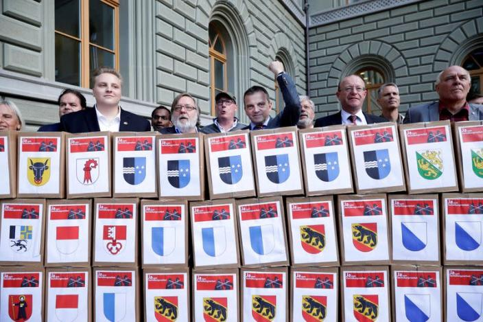 """FILE PHOTO: National Councillor Wobmann and members initiative committee for """"Yes to a Mask Ban"""" hand over boxes with signatures in Bern"""