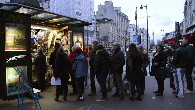 People wait outside a kiosk in Paris on January 14, 2015 as the latest edition of French satirical magazine Charlie Hebdo went on sale (AFP Photo/Bertrand Guay)