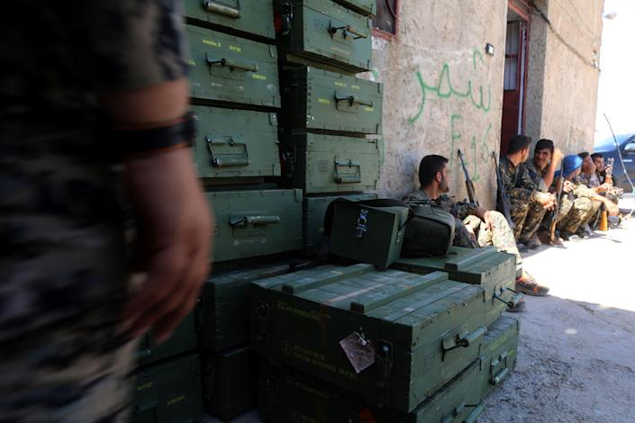 Syrian Democratic Forces, made up of an alliance of Kurdish and Arab fighters, unloaded boxes of ammunition in a village north of Raqa on June 7, 2017. (Photo: Delil Souleiman/AFP/Getty Images)