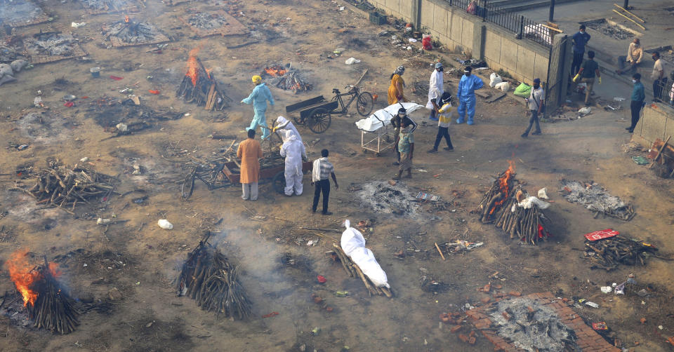 Multiple funeral pyres of those patients who died of COVID-19 disease are seen burning at a ground that has been converted into a crematorium for mass cremation of coronavirus victims, in New Delhi, India, Wednesday, April 21, 2021. (AP Photo)
