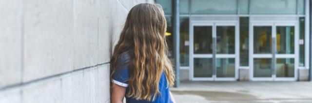 A teenager with long blond hair leaning against a wall, looking behind her.