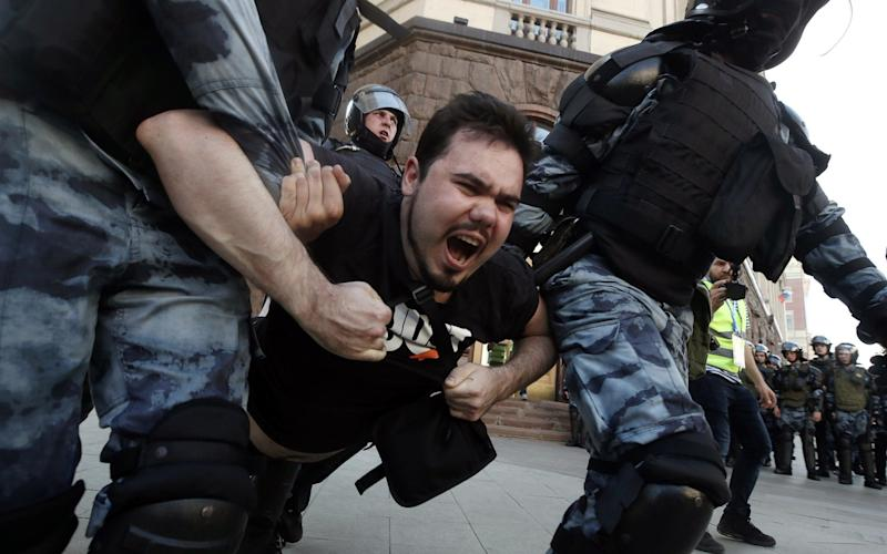 Police officers detain a man during the rally in support of rejected independent candidates - TASS