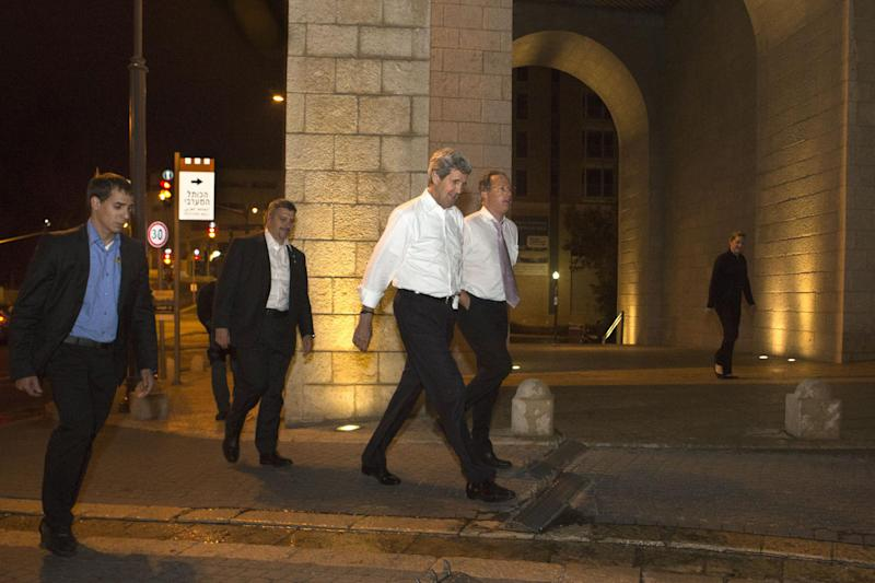 Escorted by security, U.S. Secretary of State John Kerry, center, walks with Frank Lowenstein, senior advisor to the secretary on Middle East issues, as they return to their hotel just after 4 a.m. on Sunday, June 30, 2013 after finishing a meeting with Israeli Prime Minister Netanyahu that took over six hours. After the marathon meeting, Kerry decided to get some air by walking to a park near the hotel where he is staying and the meeting was held. Kerry is shuttling between Palestinian and Israeli leaders in hopes of restarting peace talks. (AP Photo/Jacquelyn Martin, Pool)