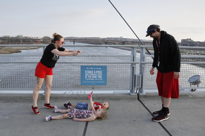In this April 6, 2020 photo, a family on the Bob Kerrey pedestrian bridge over the Missouri River take a photo of their children lying over the imaginary line between Omaha, Neb., and Council Bluffs, Iowa. As most governors have imposed stay-at-home orders that public health officials say are essential to slowing the spread of the new coronavirus, leaders in a handful of states have steadfastly refused to take the action, arguing it's unneeded and potentially harmful. (AP Photo/Nati Harnik)