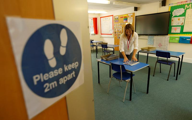 A social distancing sign is seen as teacher Rhiannon Sharman makes preparations for Watlington Primary School to reopen to children on June 1 - Eddie Keogh/Reuters