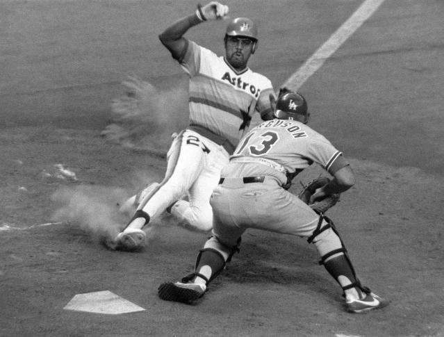 FILE - In this July 1978 file photo, Houston Astros first baseman Bob Watson (27) slides into home on a grounder by Luis Pujols, as Los Angeles Dodgers catcher Joe Ferguson (13) moves in for the tag during the sixth inning of a baseball game in Houston. Watson, a two-time All-Star as a player who later became the first African American general manager to win a World Series with the New York Yankees in 1996, has died. He was 74. (AP Photo/File)