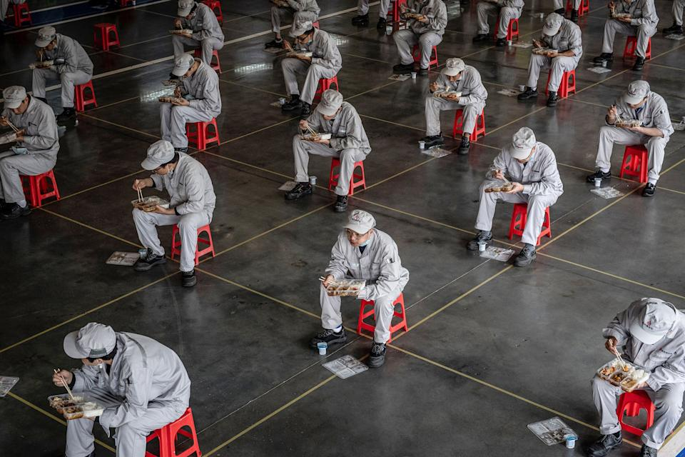 TOPSHOT - This photo taken on March 23, 2020 shows employees eating during lunch break at an auto plant of Dongfeng Honda in Wuhan in China's central Hubei province. - People in central China, where the COVID-19 coronavirus was first detected, are now allowed to go back to work and public transport has restarted, as some normality slowly returns after a two-month lockdown. (Photo by STR / AFP) / China OUT (Photo by STR/AFP via Getty Images)