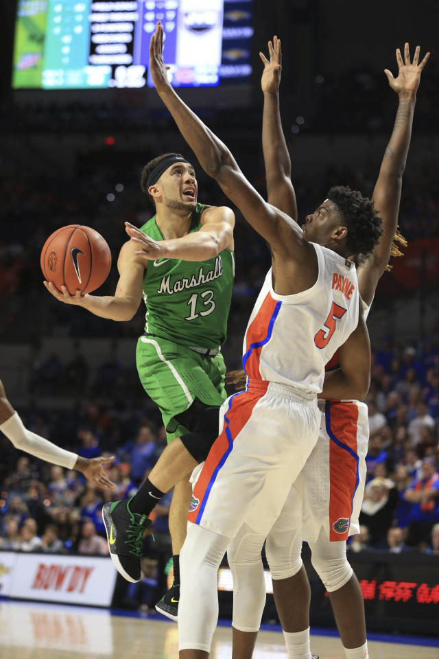 Marshall guard Jarrod West (13) takes a shot around Florida forward Omar Payne (5) during the first half of an NCAA college basketball game Friday, Nov. 29, 2019, in Gainesville, Fla. (AP Photo/Matt Stamey)