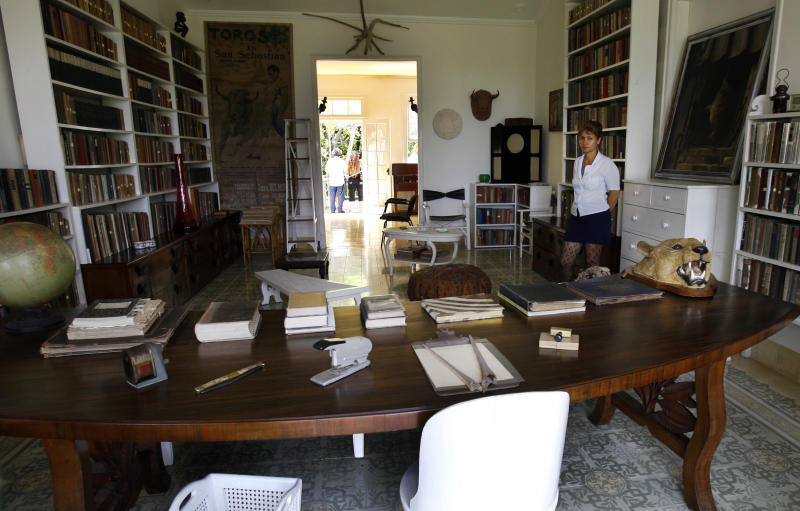 FILE - In this July 2, 2008 file photo, a museum worker stands in the library of the former home of late American writer Ernest Hemingway (1899-1961), which is open to the public as a museum in Finca Vigia, Cuba. Cuba and a private U.S. foundation are working together to preserve more of the novelist's papers and belongings that have been kept at his home near Havana since he died in 1961. The new partnership will allow U.S. scholars and the public to get a fuller view of the trove of books and records Ernest Hemingway left at his home in Cuba where he wrote some of his most famous works. The digitization of 2,000 Hemingway papers and materials will be transferred to Boston's John F. Kennedy Library. (AP Photo/Javier Galeano, File)
