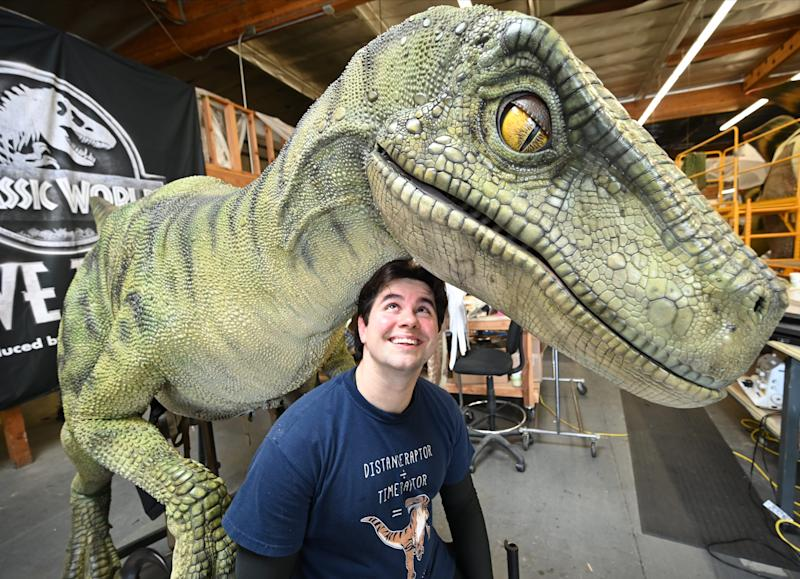 Robert Gardner is clearly a fan of dinosaurs. Here, he poses with one of the animals he controls in the