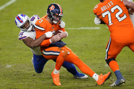 Denver Broncos quarterback Drew Lock is hauled down for a sack by Buffalo Bills defensive tackle Ed Oliver during the second half of an NFL football game Saturday, Dec. 19, 2020, in Denver. (AP Photo/David Zalubowski)