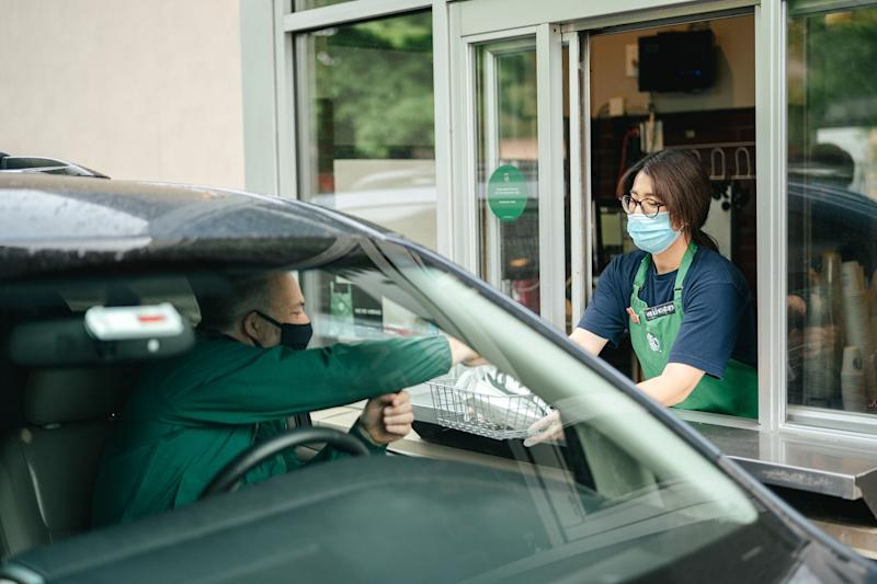 Starbucks worker serving drive-thru.