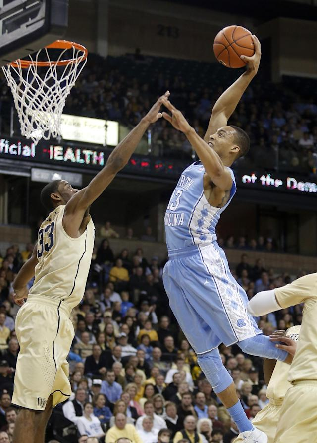 North Carolina forward J.P. Tokoto dunks over Wake Forest forward Aaron Rountree III in the second half of an NCAA college basketball game, Sunday, Jan. 5, 2014, in Winston-Salem, N.C. Wake Forest won 73-67. (AP Photo/Nell Redmond)